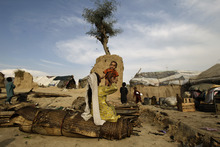 Pakistani Nori Basheer, 25, who was displaced by 2010 floods from a village near Multan, plays with her son Baber, while sitting outside her makeshift tent in a slum on the outskirts of Islamabad, Pakistan, Tuesday, April 24, 2012. (AP Photo/Muhammed Muheisen)
