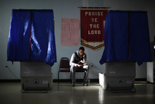 Election worker Khalid Battle reads a book as he waits for voters to cast their ballots in Pennsylvania primary election at Memorial Gospel Crusades Church, Tuesday, April 24, 2012, in Philadelphia. (AP Photo/Matt Rourke)