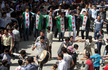 In this Friday, April 20, 2012 photo, Syrians wear revolutionary flags while they dance at a large protest in Douma, a suburb of Damascus, Syria.  A group of U.N. cease-fire observers toured a rebel-held neighborhood in the central city of Homs Saturday as residents chanted loudly for a military intervention to protect them from President Bashar Assad's regime forces. (AP Photo)