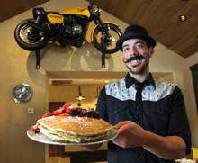 Steve Griffin | The Salt Lake Tribune Herm's Inn manager Ryan Bird holds an order of pancakes. The new Logan restaurant in a historic building has a menu that includes pancakes, omelets, breakfast skillets, hamburgers and sandwiches.