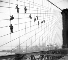 In this Oct. 7, 1914 photo provided by the New York City Municipal Archives, painters are suspended from wires on the Brooklyn Bridge in New York. Over 870,000 photos from an archive that exceeds 2.2 million images have been scanned and made available online, for the first time giving a global audience a view of a rich collection that documents life in New York City. (AP Photo/New York City Municipal Archives, Department of Bridges/Plant & Structures, Eugene de Salignac)