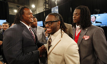 Alabama running back Trent Richardson, center, shakes hands with Alabama linebacker Dont'a Hightower, left, as Alabama cornerback Dre Kirkpatrick watches while waiting with other draft candidates before the first round of the NFL football draft at Radio City Music Hall, Thursday, April 26, 2012, in New York. (AP Photo/Jason DeCrow)