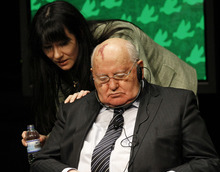 Former Soviet President Mikhail Gorbachev, right, is awakened by an unidentified woman during a panel discussion