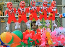 A Myanmar girl stands behind balloon toys in Yangon, Myanmar Monday, April 23, 2012. (AP Photo/Sakchai Lalit)