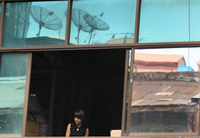 A Myanmar worker looks out from a window at her office in Yangon, Myanmar Monday, April 23, 2012. (AP Photo/Sakchai Lalit)