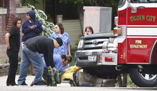 Leah Hogsten  |  The Salt Lake Tribune Bystanders and Ogden City Firefighter tend to a man lying under a vehicle after an automobile/ pedestrian accident Friday, April 27 2012 at the intersection of Harrison Blvd. and 24th Street in Ogden that occurred at 12:35p.m.