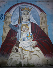 In this Sept. 16, 2010, a mural depicts an image of the Virgen Mary holding Jesus and a machine gun in a wall in La Piedrita or Little Rock neighborhood gang turf in Caracas, Venezuela.  Heavily armed gangs that pledge allegiance to President Hugo Chavez rule over fiefdoms in slums where police rarely patrol, employing vigilante justice and collecting extortion money. A shooting attack on the opposition candidate's entourage has kindled worries that Chavez's defenders could resort to violence if cancer impedes his bid for re-election. The gangs, however, are loosely organized and do not appear to be taking orders from the government. (AP Photo/Ariana Cubillos)