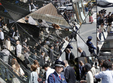 Passers-by are reflected on mirrors at a shopping center in downtown Tokyo, Tuesday, April 24, 2012.  (AP Photo/Koji Sasahara)