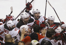 The New Jersey Devils celebrate after defeating the Florida Panthers on a goal by Adam Henrique, lower right, during the second overtime of Game 7 in a first-round NHL Stanley Cup playoff hockey series, in Sunrise, Fla., Wednesday, April 26, 2012. The Devils won 3-2. (AP Photo/J Pat Carter)