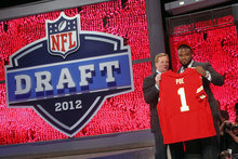 Memphis defensive tackle Dontari Poe, right, poses for photographs with NFL Commissioner Roger Goodell after being selected as the 11th pick overall by the Kansas City Chiefs in the first round of the NFL football draft at Radio City Music Hall, Thursday, April 26, 2012, in New York. (AP Photo/Jason DeCrow)