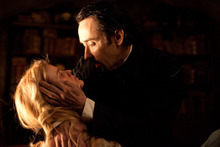 In this film publicity image released by Relativity Media, John Cusack portrays Edgar Allan Poe, right, and Alice Eve portrays Emily Hamilton in a scene from the gothic thriller