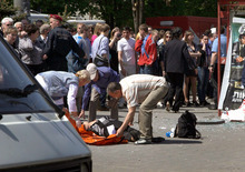People assist an injured person after an explosion in Dnipropetrovsk, Ukraine, Friday, April 27, 2012. Officials say four blasts within minutes have rocked the center of the eastern Ukrainian city of Dnipropetrovsk, injuring dozens of people, including schoolchildren, in what prosecutors believed was a terrorist attack. (AP Photo/Dmitriy Dvorsky)