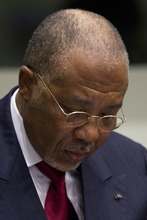 Former Liberian President Charles Taylor takes notes as he waits for the start of a hearing to deliver verdict in the court room of the Special Court for Sierra Leone in Leidschendam, near The Hague, Netherlands, Thursday April 26, 2012. Judges were expected to deliver landmark judgements in the trial against the former president who is charged with supporting notoriously brutal rebels in neighboring Sierra Leone. (AP Photo/Peter Dejong, Pool)