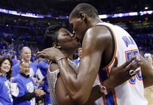 Fans watch at left as Oklahoma City Thunder's Kevin Durant, right, kisses his mother, Wanda Pratt, after the Thunder defeated the Dallas Mavericks 99-98 in Game 1 of a first-round NBA basketball playoff series in Oklahoma City, Saturday, April 28, 2012. (AP Photo/Sue Ogrocki)
