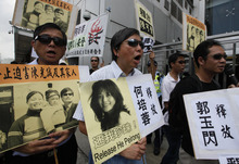 Pro-democracy protesters wearing sunglasses, hold placards with picture of  blind Chinese legal activist Chen Guangcheng, third left, with his family and Chinese activist He Peirong, right,  outside the China's Liaison Office in Hong Kong Monday, April 30, 2012 as they urge Beijing government stop persecution of Chen. A U.S. rights campaigner says a deal securing U.S. asylum for a blind Chinese legal activist who fled house arrest is expected in the coming 24 to 48 hours.  (AP Photo/Kin Cheung)