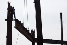 In this March 23, 2012, photo ironworkers connects steel beams at the top of One World Trade Center in New York. One World Trade Center, the giant monolith being built to replace the twin towers destroyed in the Sept. 11 attacks, will lay claim to the title of New York City's tallest skyscraper on Monday, April 30, as workers erect steel columns that will make its unfinished skeleton a little over 1,250 feet, just high enough to peak over the observation deck on the Empire State Building. The milestone is a preliminary one. The so-called