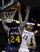 San Antonio Spurs' Tim Duncan (21) scores over Utah Jazz's Paul Millsap (24) during the fourth quarter of Game 1 of a first-round NBA basketball playoff series on Sunday, April 29, 2012, in San Antonio. San Antonio won 106-91.(AP Photo/Eric Gay)