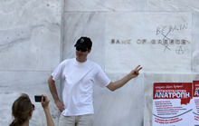 Tourists take a photograph outside Bank of Greece headquarters after protesters wrote ''Bank of Berlin'' during a May Day protest in Athens, Tuesday, May 1, 2012. In debt-crippled Greece, more than 2,000 people marched through central Athens in subdued May Day protests centered on the country's harsh austerity program. (AP Photo/Thanassis Stavrakis)