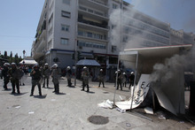 Riot police stand next to a burning election kiosk of an independent right-wing candidate by protesters during a May Day protest in Athens, Tuesday, May 1, 2012. In debt-crippled Greece, more than 2,000 people marched through central Athens in subdued May Day protests centered on the country's harsh austerity program.  (AP Photo/Thanassis Stavrakis)