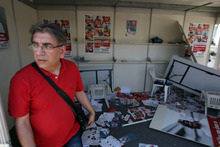 A member of Democratic Left party leaves the destroyed election kiosk by protesters during a May Day protest in Athens, Tuesday, May 1, 2012. In debt-crippled Greece, more than 2,000 people marched through central Athens in subdued May Day protests centered on the country's harsh austerity program. The Greek elections are scheduled for Sunday, May 6. (AP Photo/Thanassis Stavrakis)
