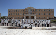 Protesters hold placards reading ''No Nazis in Parliament, Golden Dawn=Swastika'', outside the Greek Parliament during a May Day protest in Athens, Tuesday, May 1, 2012.  In debt-crippled Greece, more than 2,000 people marched through central Athens in subdued May Day protests centered on the country's harsh austerity program. The Greek elections are scheduled for Sunday, May 6. (AP Photo/Thanassis Stavrakis)