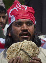 A Pakistani worker holds stale bread locally called 'roti',  as he shouts slogans during a rally to mark May Day in Islamabad, Pakistan on Tuesday, May 1, 2012. Pakistani workers also observed the International Labors Day along with other nations worldwide. (AP Photo/Anjum Naveed)