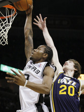 San Antonio Spurs' Kawhi Leonard, left, shoots above Utah Jazz forward Gordon Hayward during the first half of an NBA basketball game on Saturday, Dec. 31, 2011, at the AT&T Center in San Antonio. (AP Photo/Darren Abate)