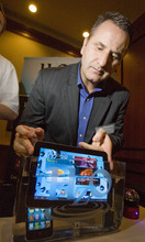 Fraughton Photography  Rick Peterson, of HzO Inc. slides an I Pad along with an IPhone into a small tank of water to demonstrate his company's  WaterBlock (tm) technology which protects electronic devices from water. Company literature describes the WaterBlock as,