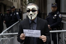 A demonstrator wears a maks outside of the Wells Fargo shareholders meeting in San Francisco,  Tuesday, April 24, 2012. Police were guarding the entrance to the annual meeting of Wells Fargo shareholders on Tuesday as protesters associated with the Occupy Wall Street movement geared up to crash the gathering. Bank stockholders were asked to show certificates or other proof of ownership before being corralled past gates erected in front of the doors. (AP Photo/Marcio Jose Sanchez)