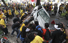 Protesters overturn a police car during a rally to demand for electoral reforms in Kuala Lumpur, Malaysia, Saturday, April 28, 2012. Police unleashed tear gas and chemical-laced water at thousands of demonstrators who staged one of Malaysia's largest street rallies in years, demanding fair rules for national elections expected soon. (AP Photo) MALAYSIA OUT