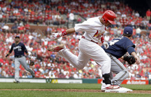 St. Louis Cardinals' Jon Jay, center, beats out a throw from Milwaukee Brewers third baseman Aramis Ramirez, left, as Mat Gamel, right, covers first during the fifth inning of a baseball game Saturday, April 28, 2012, in St. Louis. (AP Photo/Jeff Roberson)