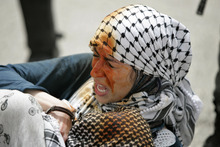 A demonstrator grimaces after she was pepper sprayed by Israeli troops during a protest calling for the release prisoners jailed in Israel outside the Ofer military prison, near the West Bank city of Ramallah, Tuesday May 1, 2012.  (AP Photo/Majdi Mohammed)
