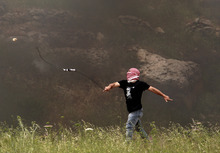 A masked Palestinian hurls a stone at Israeli troops, unseen, during a protest calling for the release prisoners jailed in Israel outside the Ofer military prison, near the West Bank city of Ramallah, Tuesday May 1, 2012. (AP Photo/ Nasser Shiyoukhi)