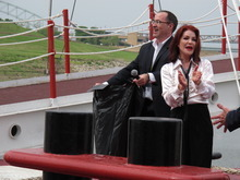 Priscilla Presley, the former wife of late rock and roll icon Elvis Presley, claps after smashing a champagne bottle to christen the American Queen riverboat as it resumes travel on the Mississippi River on Friday, April 27, 2012 in Memphis, Tenn. At left is Tim Rubacky, an executive with the Great American Steamboat Company. (AP Photo/Adrian Sainz)
