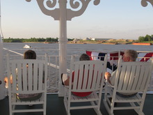 In this April 27, 2012 photo, passengers on the American Queen steamboat take in the view as they sit on rocking chairs as the vessel moves up the Mississippi River in Memphis, Tenn. The American Queen is the largest steamboat in the world, carrying 436 passengers. The 418-foot-long vessel is taking tourists on long-distance trips on the Mississippi for the first time since 2008, when its previous owner ceased operations. (AP Photo/Adrian Sainz)