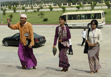 Myanmar pro-democracy leader Aung San Suu Kyi, center, arrives at the parliament building to attend a regular session of Myanmar Lower House, in Naypyitaw, Myanmar, Wednesday, May 2, 2012. Suu Kyi was set to be sworn in to Myanmar's military-backed parliament Wednesday to take public office for the first time since launching her struggle against authoritarian rule nearly a quarter century ago. Others are unidentified. (AP Photo/Khin Maung Win)
