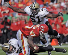 This Nov. 16, 2008 file photo shows New Orleans Saints linebacker Jonathan Vilma (51) flying in to help stop Kansas City Chiefs running back Larry Johnson (27) as he's tied up by New Orleans Saints linebacker Scott Fujita, lower left, late in the second quarter of an NFL football game in Kansas City, Mo. Vilma has been suspended without pay for the entire 2012 season by the NFL, one of four players punished for participating in a pay-for-pain bounty system. NFL Commissioner Roger Goodell's ruling was announced Wednesday, May 2, 2012 . (AP Photo/Reed Hoffmann, File)