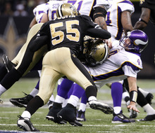This Jan. 24, 2010, file photo shows Minnesota Vikings quarterback Brett Favre (4) being hit by New Orleans Saints linebacker Scott Fujita (55) and Anthony Hargrove during the fourth quarter of the NFC Championship NFL football game in New Orleans. Saints linebacker Jonathan Vilma has been suspended without pay for the entire 2012 season by the NFL, one of four players punished for participating in a pay-for-pain bounty system. Defensive lineman Anthony Hargrove, now with the Green Bay Packers, is suspended for eight games this season; Saints defensive end Will Smith is barred for four games; and linebacker Scott Fujita, now with the Cleveland Browns, will miss three games. All of the suspensions are without pay. (AP Photo/Mark Humphrey, File)