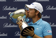 Bernd Wiesberger of Austria kisses the trophy after winning the Ballantine's Championship golf tournament at the Black Stone Golf Club in Icheon, South Korea, Sunday, April 29, 2012. (AP Photo/Lee Jin-man)