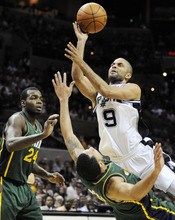 San Antonio Spurs' Tony Parker (9), of France, shoots over Utah Jazz's Devin Harris and Paul Millsap (24) during the second half of an NBA basketball game, Sunday, April 8, 2012, in San Antonio. (AP Photo/Darren Abate)