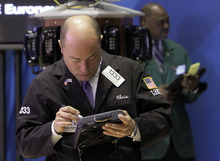 Trader Christopher Morie, left, works on the floor of the New York Stock Exchange, Monday, April 9, 2012, in New York. Wall Street appeared headed for a flat open Thursday May 3, 2012, with Dow Jones industrial futures nearly unchanged at 13,206. S&P 500 futures were marginally higher at 1,398.30. (AP Photo/Richard Drew)