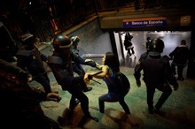 A police officer in riot gear beats a girl who was taking part in celebrations after Real Madrid won the Spanish Soccer La Liga at the Spain's Bank Metro station in Madrid, Thursday, May 3, 2012. Madrid won 3-0 at Athletic Bilbao on Wednesday for its first league championship since 2008, forcing Barcelona to relinquish the title after three straight years. Jose Mourinho became the first coach to win titles in four different European leagues. (AP Photo/Daniel Ochoa de Olza)