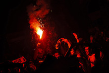 Real Madrid's soccer team supporters light a flare as they celebrate after Real Madrid won the Spanish Soccer La Liga at Cibeles square in Madrid, Thursday, May 3, 2012. Madrid won 3-0 at Athletic Bilbao on Wednesday for its first league championship since 2008, forcing Barcelona to relinquish the title after three straight years. Jose Mourinho became the first coach to win titles in four different European leagues. (AP Photo/Daniel Ochoa de Olza)