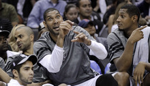 San Antonio Spurs' Tim Duncan, center, reacts on the bench during the fourth quarter of Game 2 of a first-round NBA basketball playoff series against the Utah Jazz, Wednesday, May 2, 2012, in San Antonio. San Antonio won 114-83. Tony Parker, of France, is at left, and Boris Diaw, of France, is right. (AP Photo/Eric Gay)