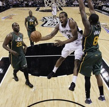 San Antonio Spurs' Kawhi Leonard (2) drives to the basket as Utah Jazz's Josh Howard (8) and Al Jefferson (25) defend during the first quarter of Game 2 of a first-round NBA basketball playoff series, Wednesday, May 2, 2012, in San Antonio. (AP Photo/Eric Gay)