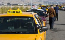 Al Hartmann  |  Tribune file photo Taxi drivers queue up for fares south of Salt Lake City International Airport. Two local cab companies that were passed over for contracting for on-demand services to two out-of-state firms are challernging the decision.