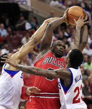 Chicago Bulls' Luol Deng (9) looks to pass the ball as he is defended by Philadelphia 76ers' Lou Williams (23) and Andre Iguodala during the first quarter of Game 3 in an NBA basketball first-round playoff series in Philadelphia, Friday, May 4, 2012. (AP Photo/Mel Evans)
