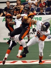Kim Raff | The Salt Lake Tribune Utah Blaze player Chris Bocage catches a pass over the heads of Spokane Shock players (left) Paul Stephens and Josh Ferguson during a game at the EnergySolutions Arena in Salt Lake City, Utah on May 4, 2012.
