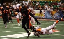 Kim Raff | The Salt Lake Tribune Utah Blaze player Maurice Bryant makes a run but is tripped up by Spokane Shock player Josh Ferguson during a game at the EnergySolutions Arena in Salt Lake City, Utah on May 4, 2012.