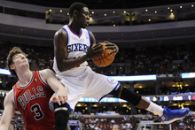 Philadelphia 76ers' Jrue Holiday (11) pulls in a rebound over Chicago Bulls' Omer Asik, of Turkey, during the first half of Game 4 in a first-round NBA basketball playoff series, Sunday, May 6, 2012, in Philadelphia. (AP Photo/Michael Perez)